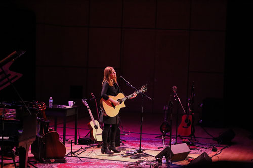 Carrie Newcomer playing guitar in Sauder Hall