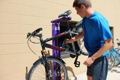 A student brings their bike to the new purple Goshen bike repair station