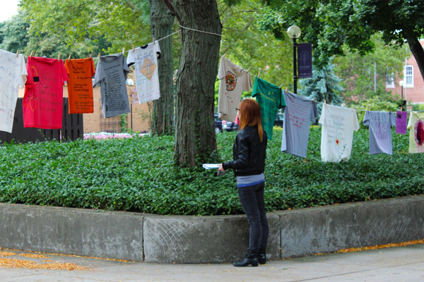 A student stands in Schrock Plaza and looks at the T-shirts hanging on clotheslines. The shirts vary in color and size