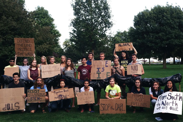 Students and community members hold up cardboard signs bearing anti-pipeline messages