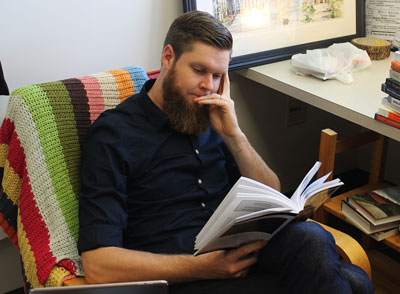 Philip Gollner rests his face in one hand and holds a book in the other. The chair he is sitting in is covered in a brightly colored, striped blanket