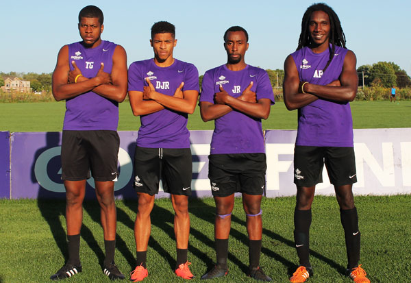 Ari Benjamin, Tevin Gilkes, Jimmelle Ramikissoon and Darius Rawlins pose with crossed arms on the Goshen College soccer field. They are all wearing purple Goshen jerseys
