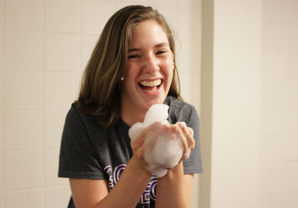 Abby King laughs over a handful of foam and bubbles