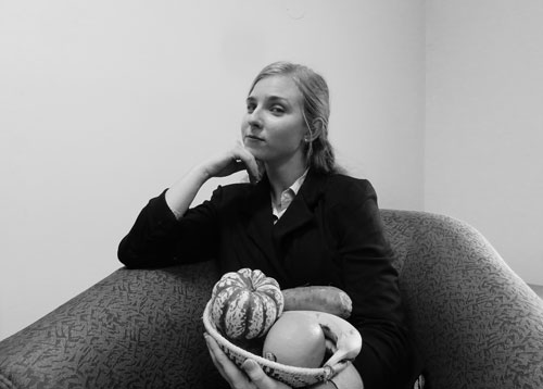 Hannah Thill poses for a picture with a basket of fruit