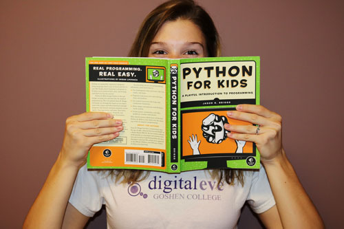 """A woman wearing a """"Digital Eve Goshen College"""" T-shirt covers her face with a book titled """"Python for Kids"""""""