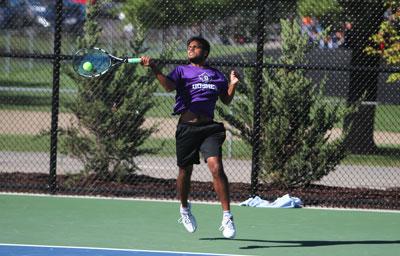 Tennis player swings to return ball