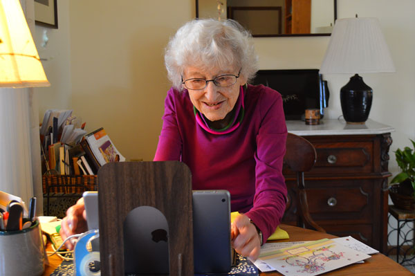 Evelyn Kreider smiles at something on the iPad on her table. She is in a well-lit living room decorated with lamps, books, and more