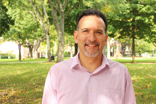 Outdoor portrait of a smiling Gilberto Perez; the Goshen College campus can be seen in the background