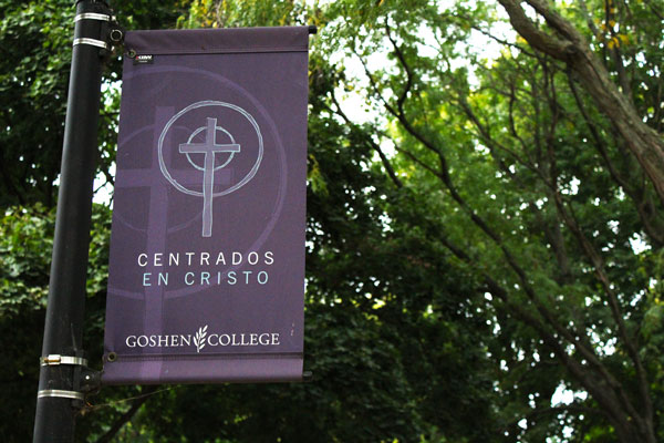 """A purple Goshen College banner reads """"Centrados en Cristo"""" and features an image of a cross"""