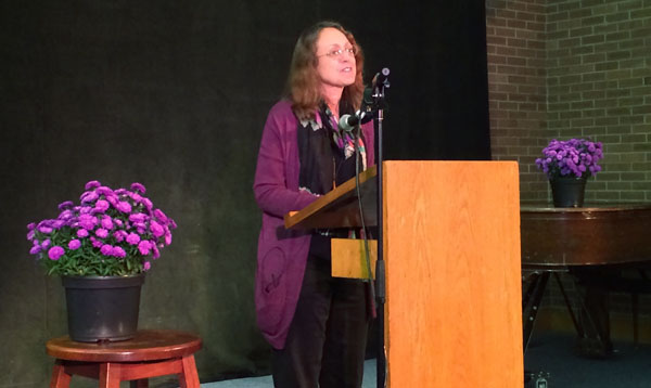Shari Wagner speaks into a microphone at a podium. A small table and a pot of purple flowers are on either side of her, and she is earing a purple cardigan