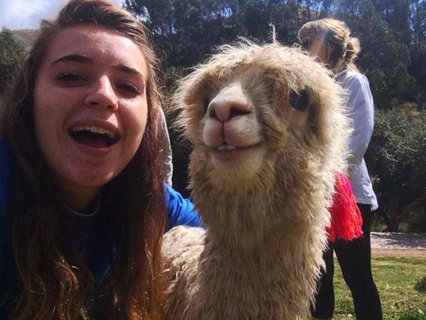 Katie Hurst takes a selfie with an alpaca in Peru