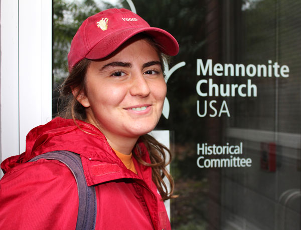 """Katie Yoder takes a selfie with a """"Mennonite Church USA Historical Committee"""" logo"""