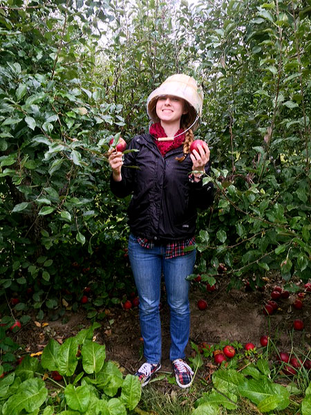 Hannah Thill picks apples in an orchard with a bucket over her head