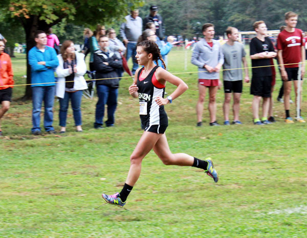 Chelsea Foster runs down a cross country course