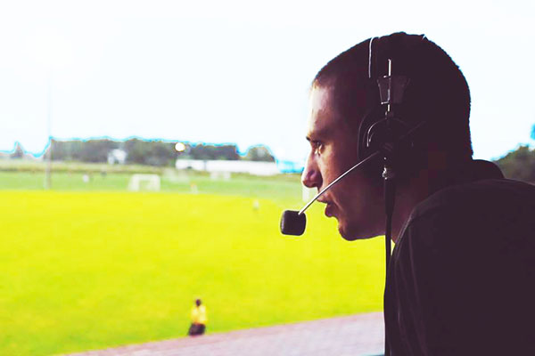Close-up image of Dalton Shetler wearing a microphone headset while calling a game. The game field is in the background of the shot