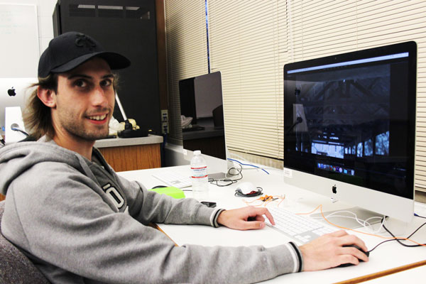 Mason Mellinger turns to the camera as he works on a film project on a computer at his desk