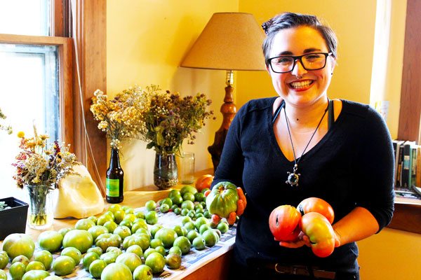 Naomi Gross holds red and green tomatoes in both hands. Beside her is a table full of more green tomatoes