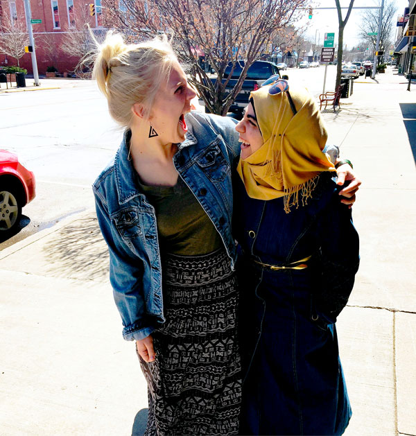Sara Azzuni and another student embrace and laugh together