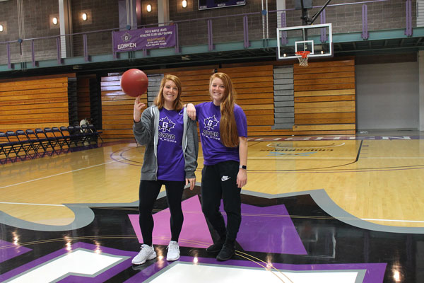 Carley and Caitlyn O'Neal wear Goshen College T-shirts while posing for a picture in the RFC gym. One of the sisters balances a basketball on her finger