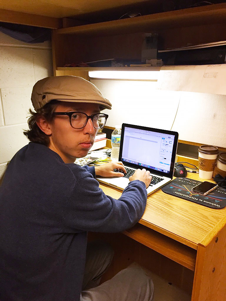 Isaac Longenecker turns to face the camera while working on his laptop