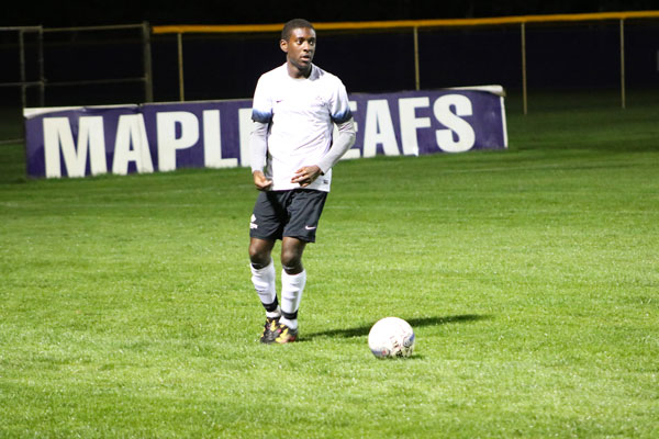 """Ethan Francois-Ravalier dribbles the soccer ball down the Goshen College field. A large """"Maple Leafs"""" sign is in the background of the shot"""