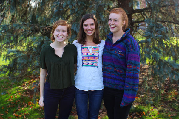 three seniors pose for photo by a tree