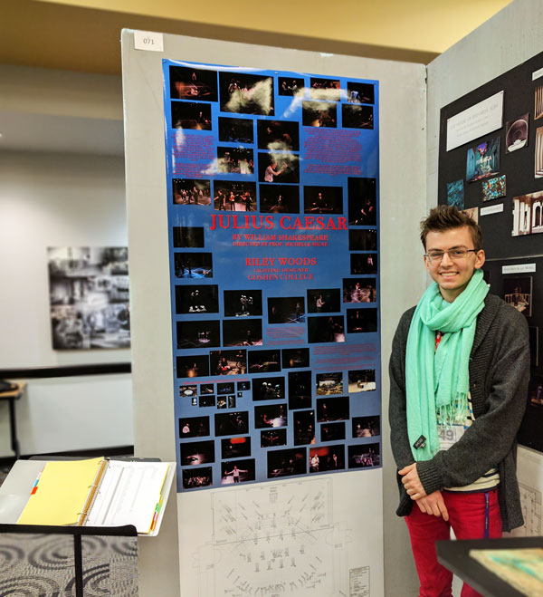 A theater student poses next to a Julius Caesar poster
