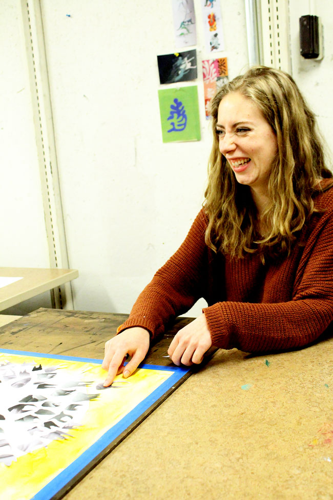 Katie McKinnell laughs and points at a piece of artwork