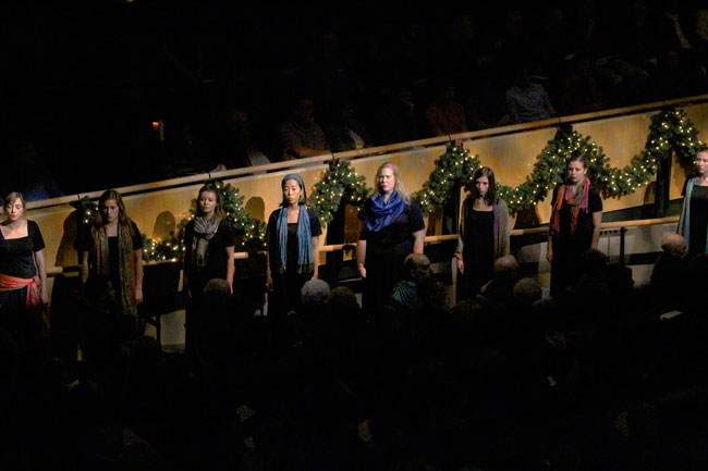 The Goshen Women's Choir is illuminated by a spotlight during a concert in Sauder Concert Hall
