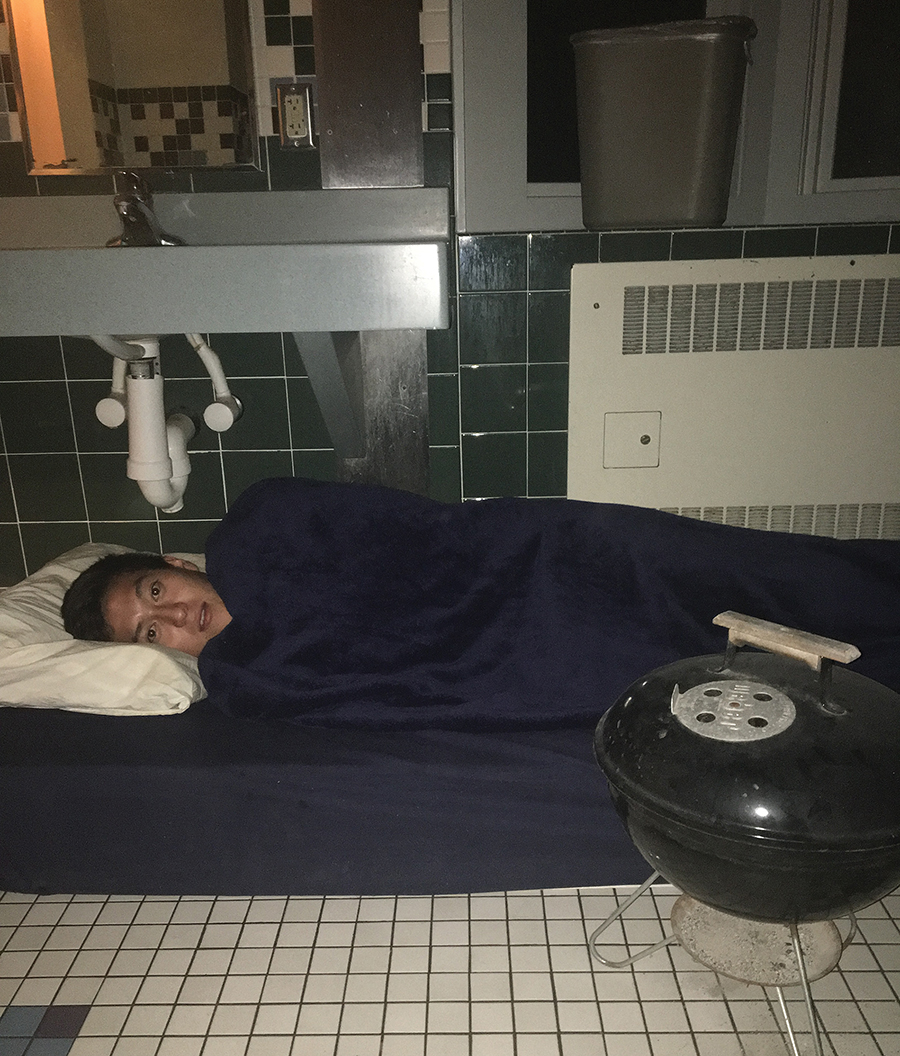A student sleeps under a sink in the dorm bathrooms