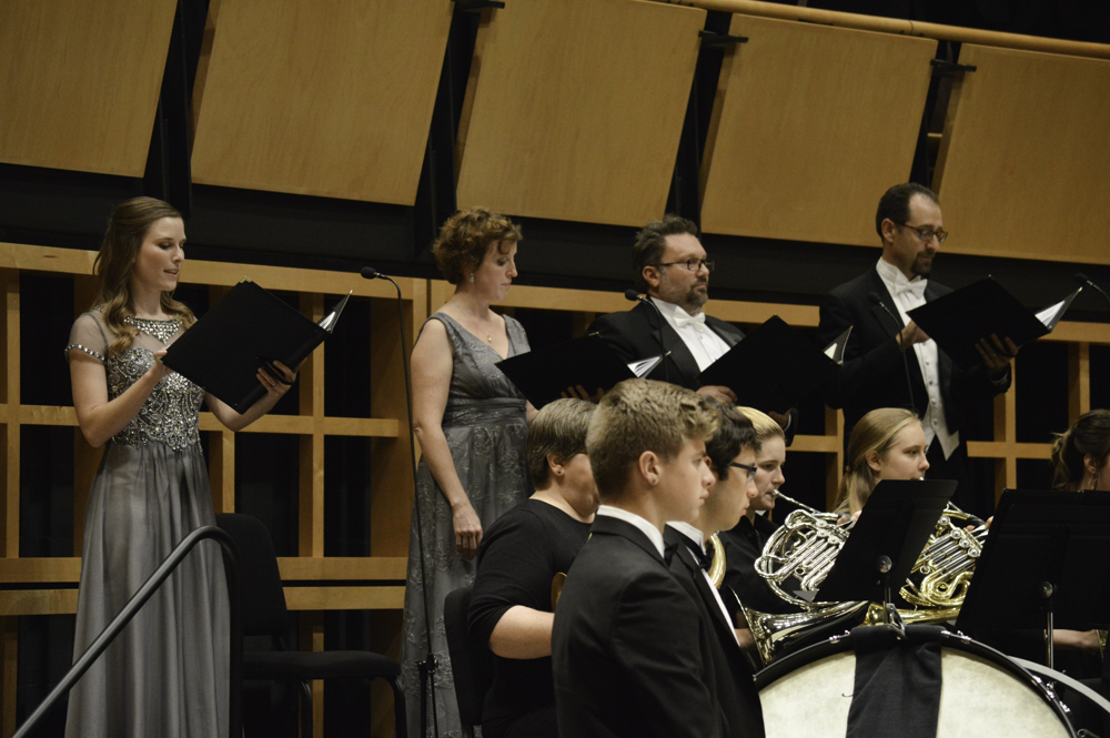 Goshen choir member sing onstage with the Goshen Symphony Orchestra
