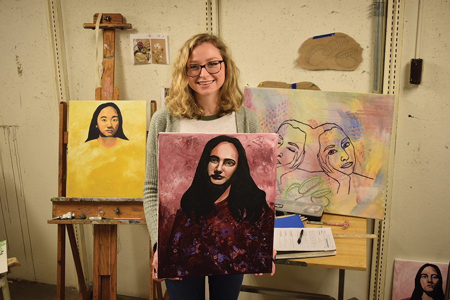 Maddy Keener poses for a picture with three of her paintings