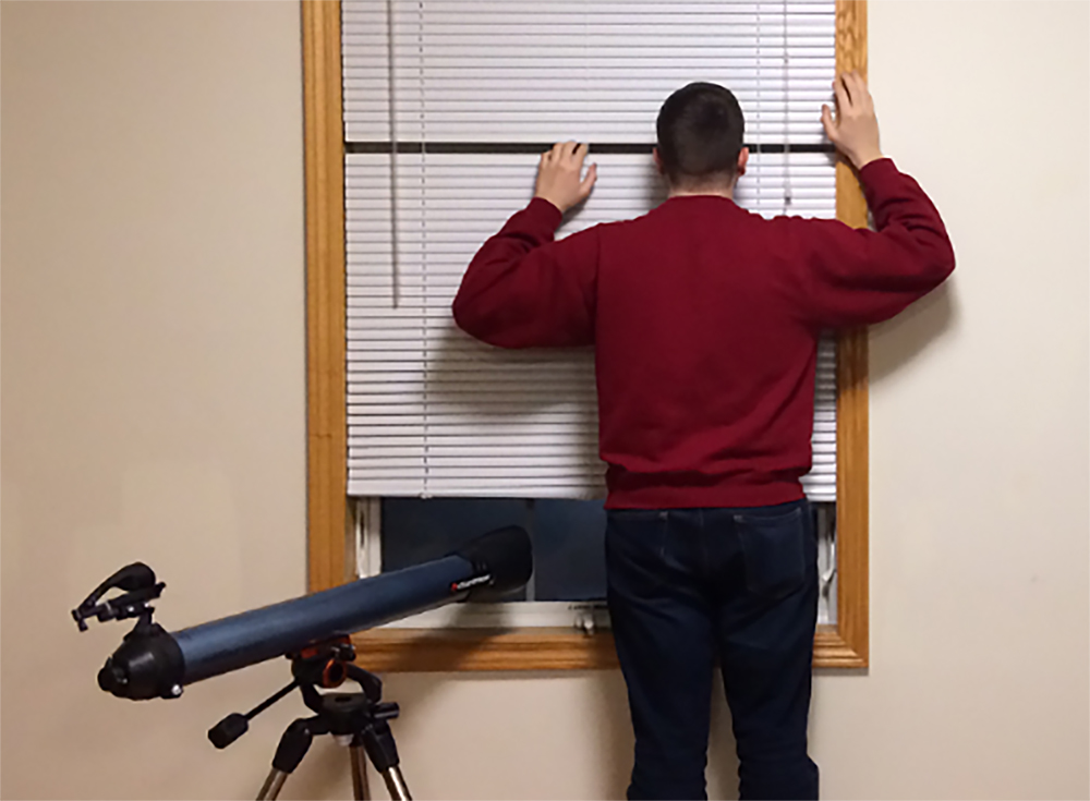 A man in a red coat looks out the window through a crack in the window shades