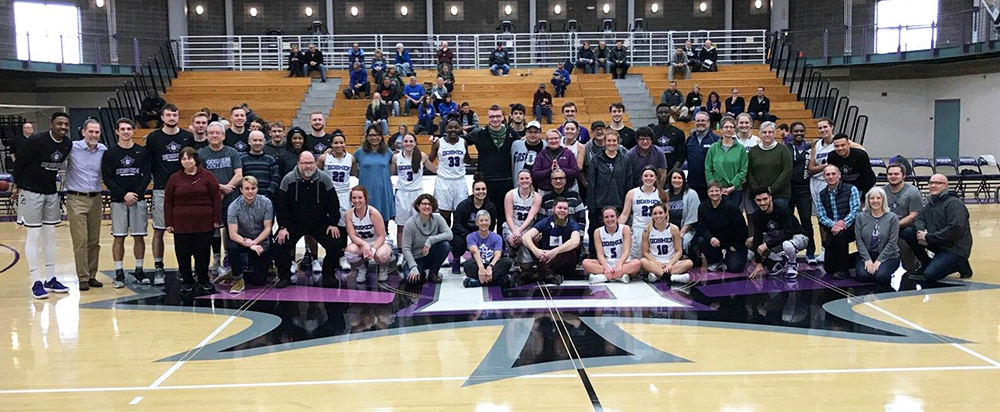 Basketball teams group with professors for a photo