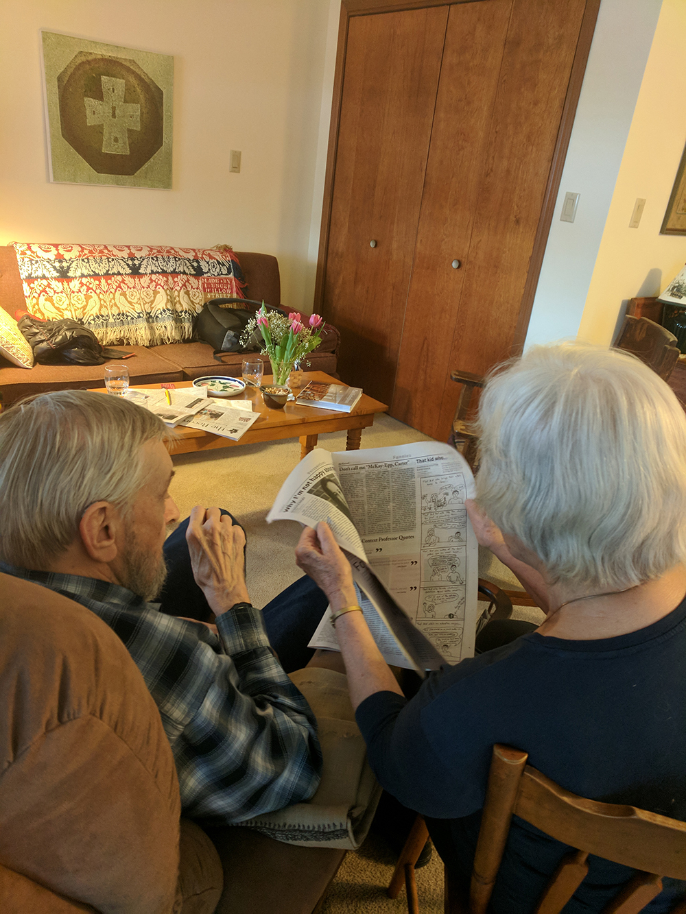 Couple looks at newspaper together