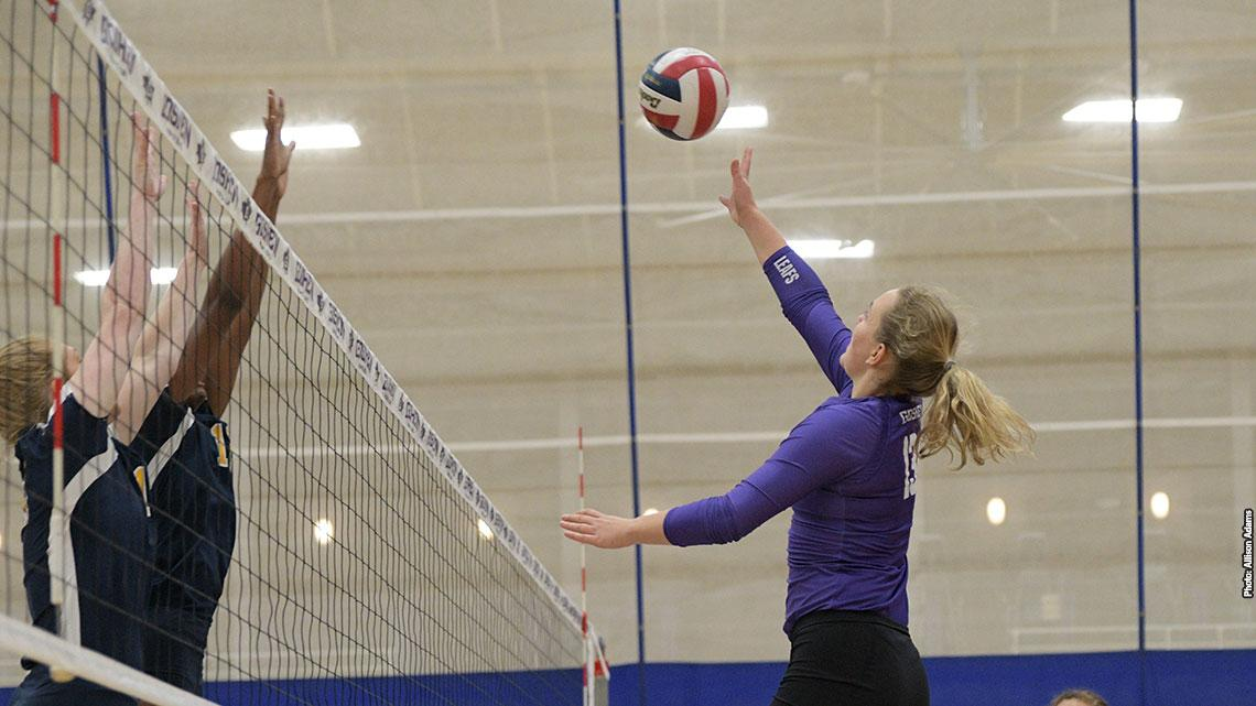 volleyball player hits ball over net