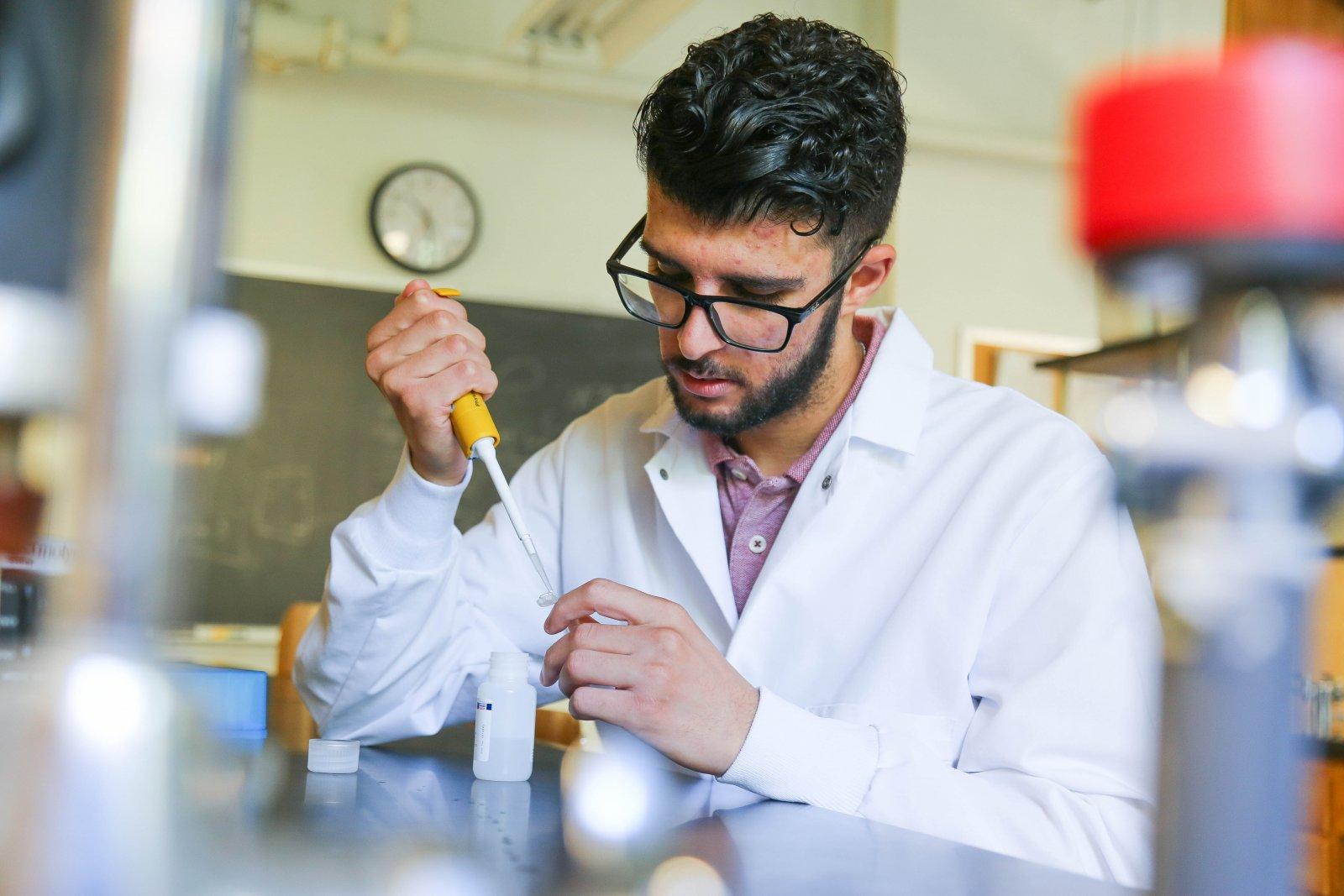 Yazan Meqbil works in science lab