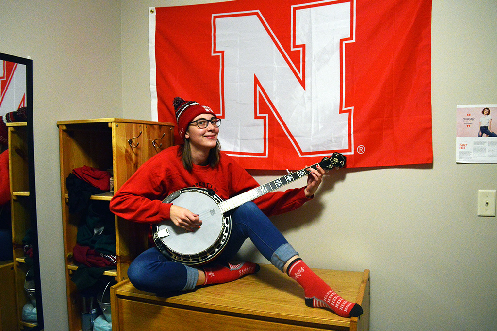 Kristin Troyer plays the banjo next to a red Nebraska flag