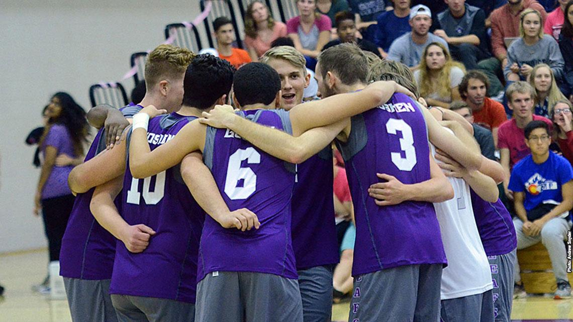 Volleyball team huddles on the court