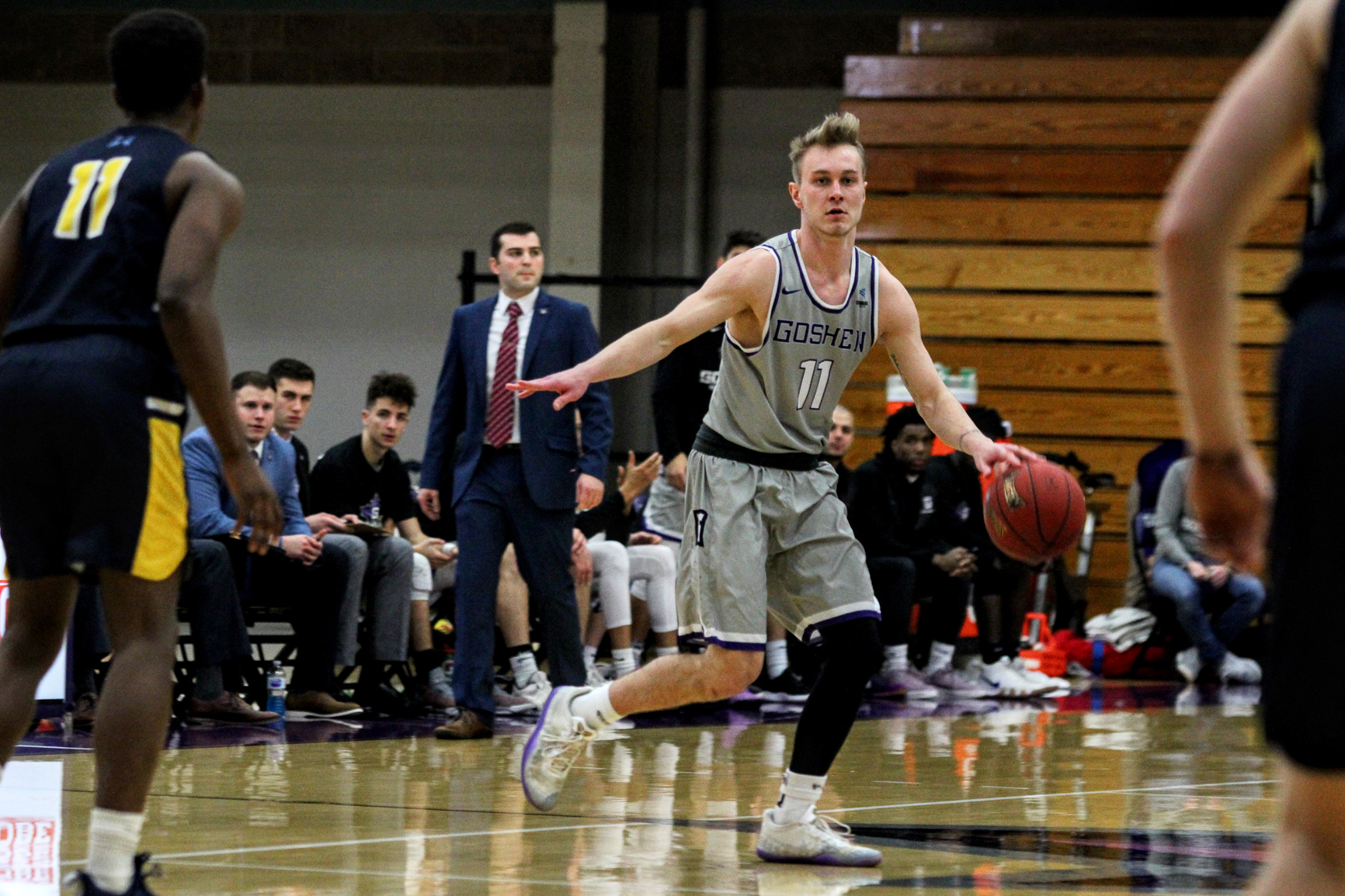 A player on the Goshen men's basketball team dribbles the ball down the court during a game