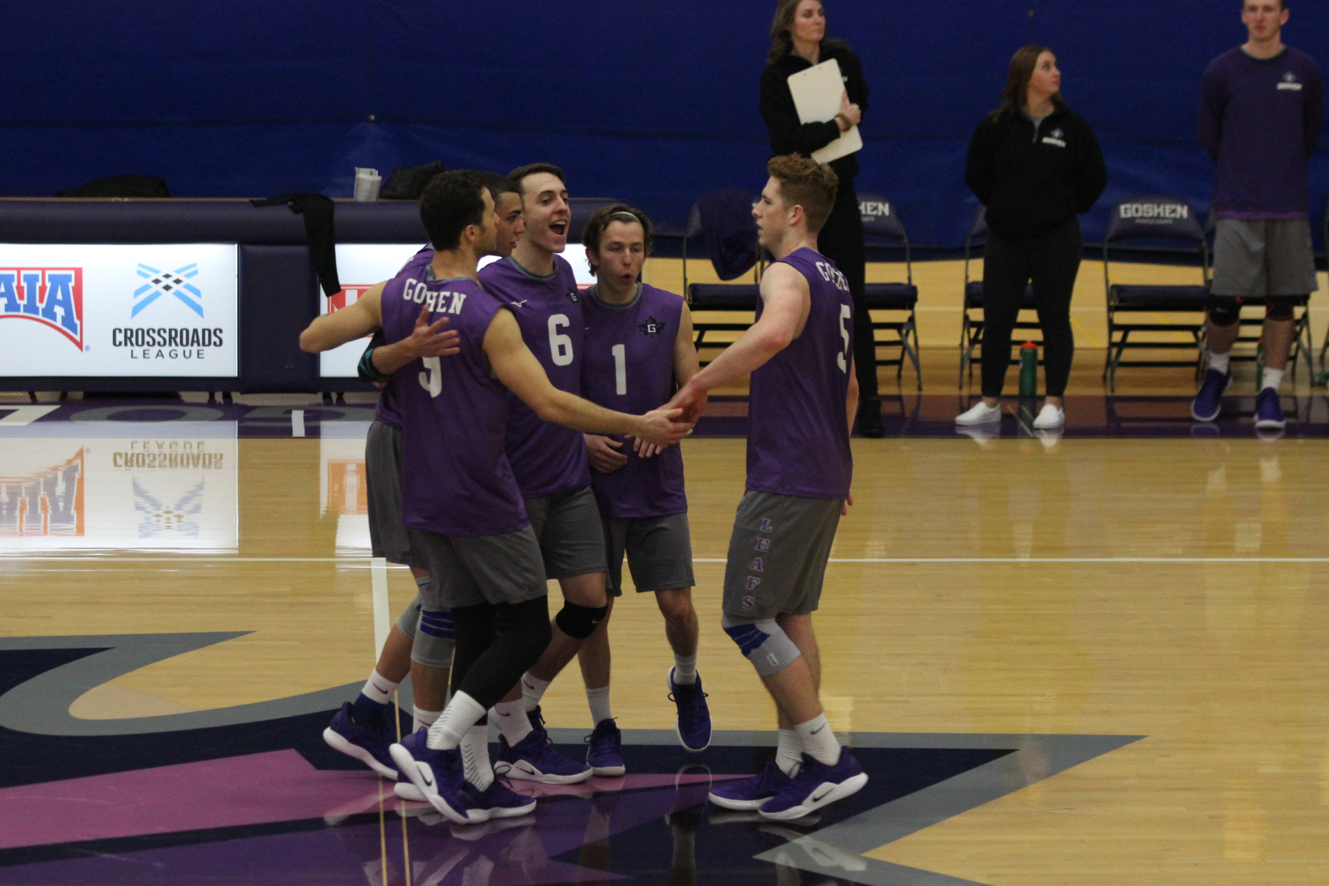 Four members of the Goshen men's volleyball team celebrate a winning point during a game