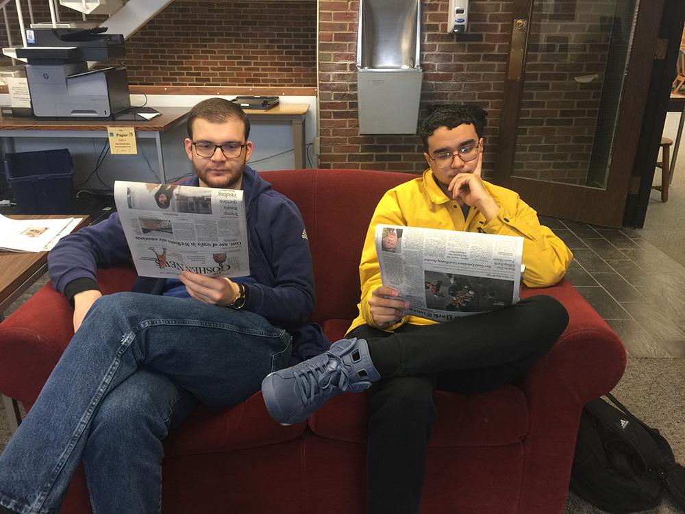 Nahshon Lora and Rudi Mucaj read newspapers