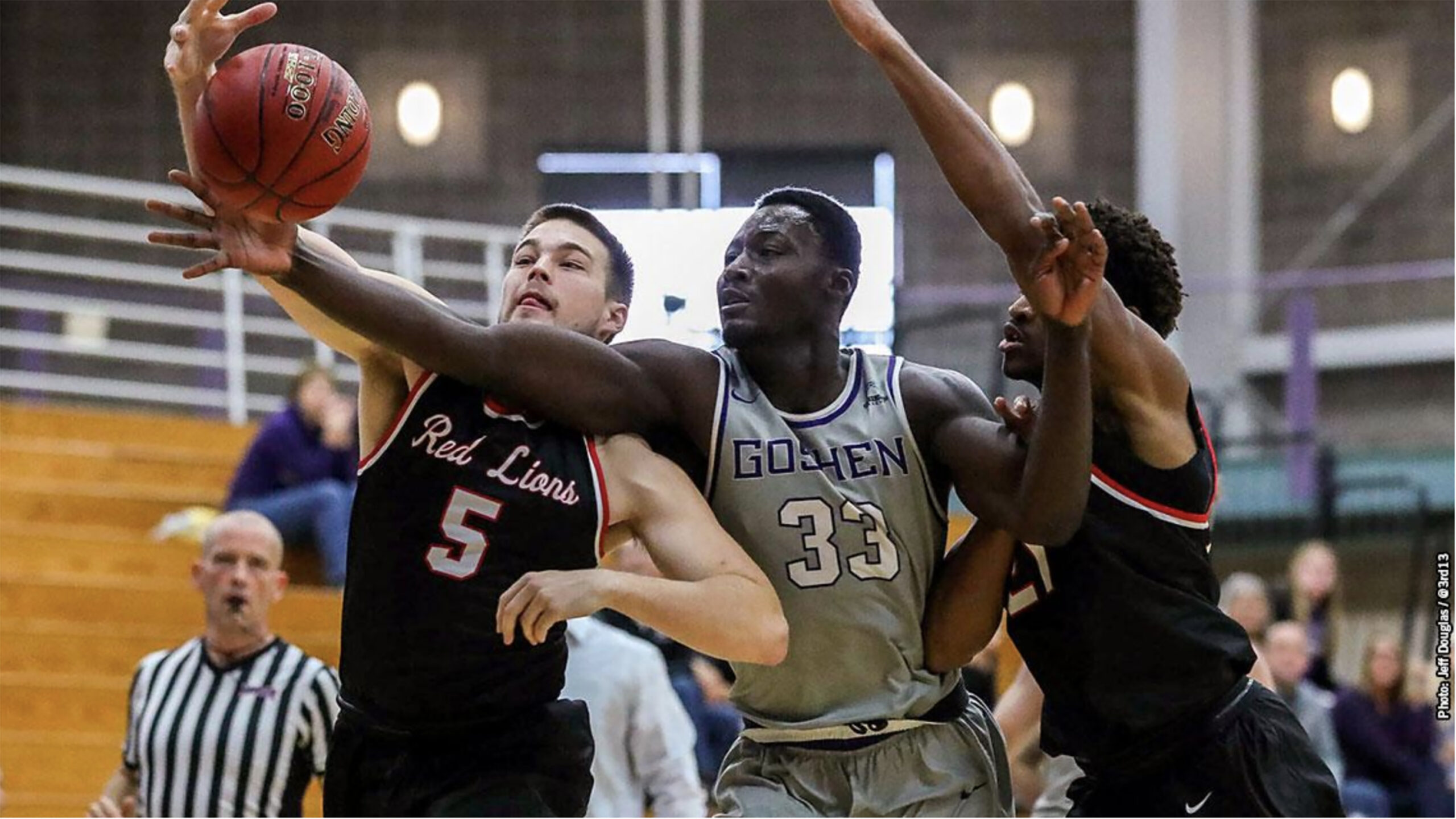 A player on the Goshen men's basketball team struggles to keep the ball away from two opposing players
