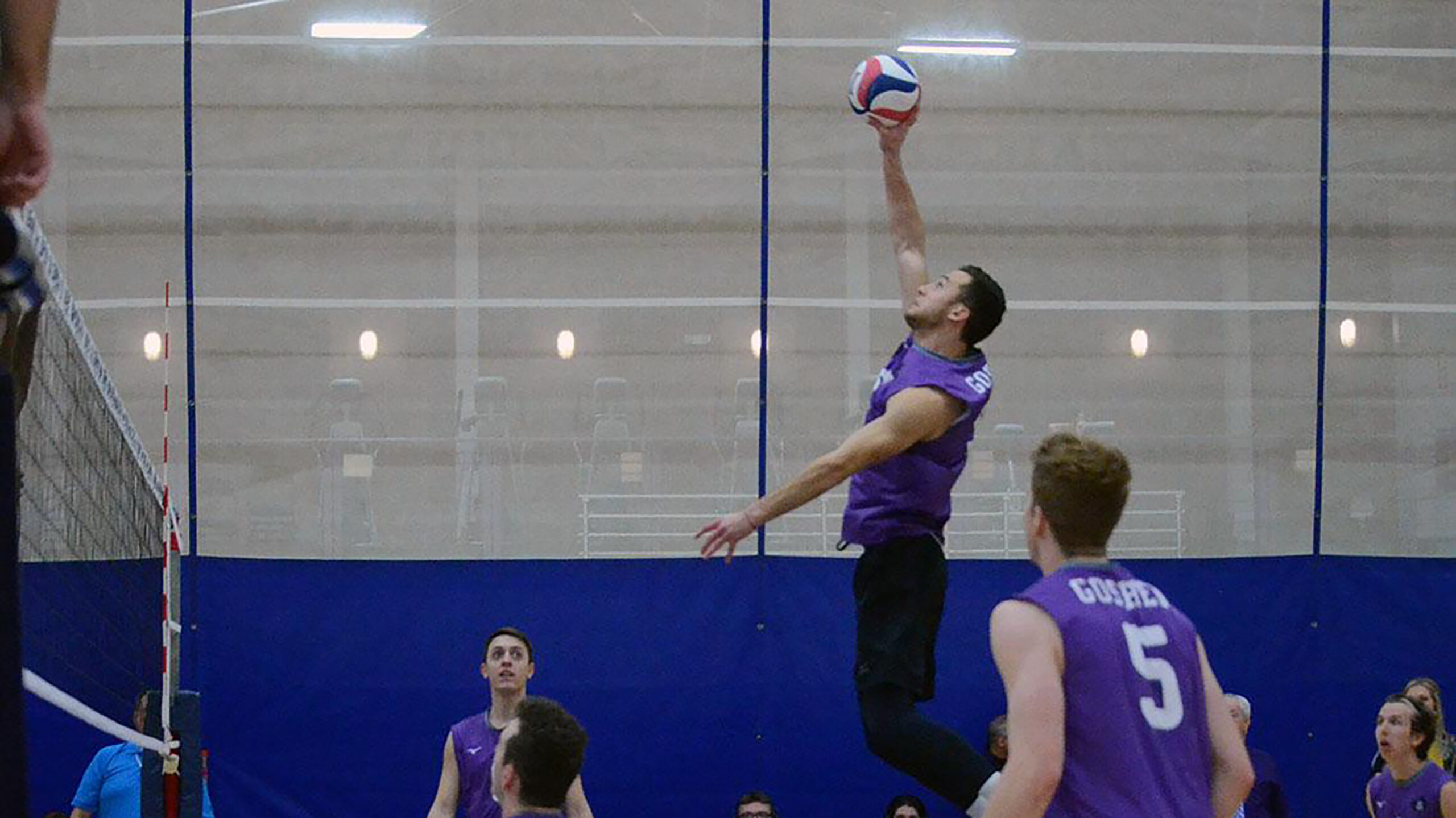 A player on the Goshen men's volleyball team jumps to hit the ball during a game