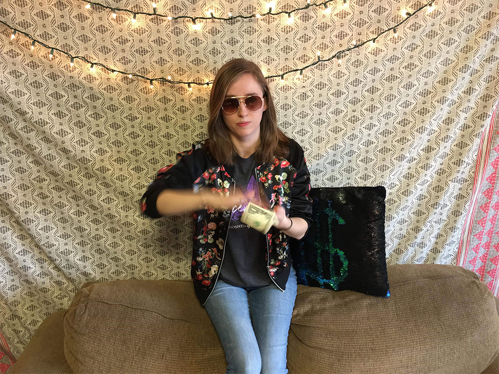 Kelsey Winters wears sunglasses and waves a one dollar bill