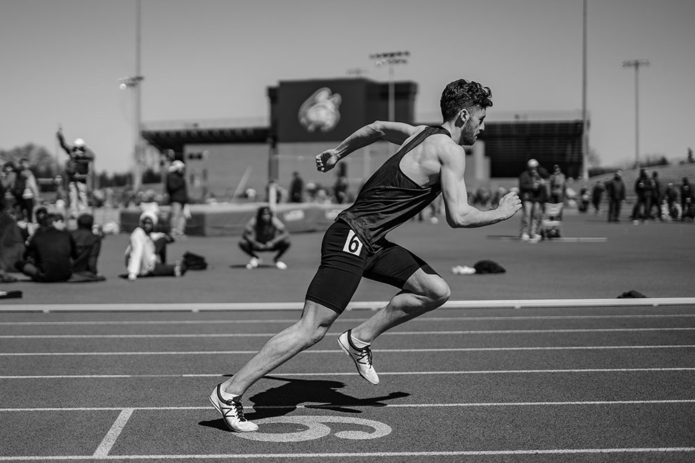 Black and white image of Ollie Smith competing in the 400m sprint