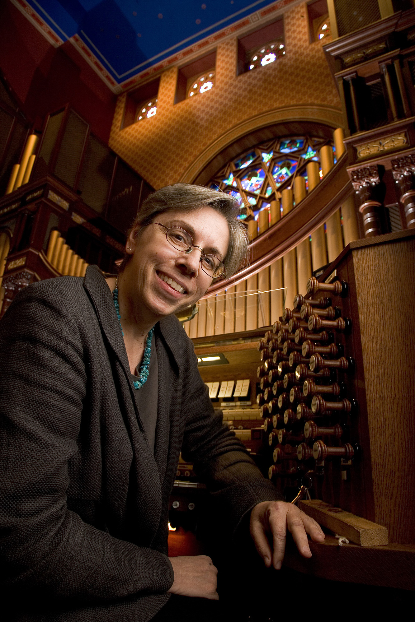 Archer Gail poses for a picture next to an organ