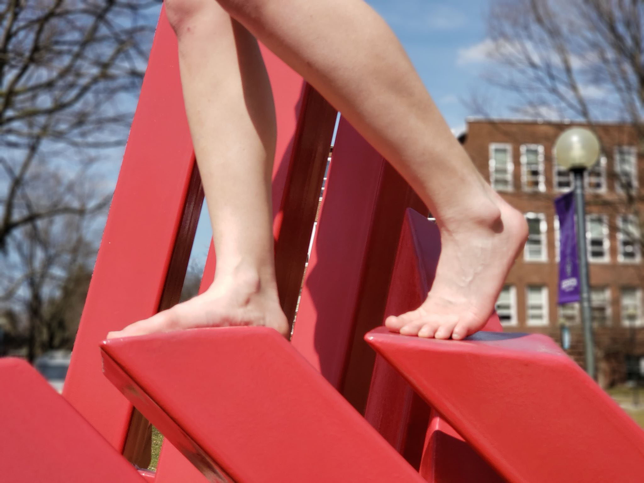 Bare feet stand on campus sculpture