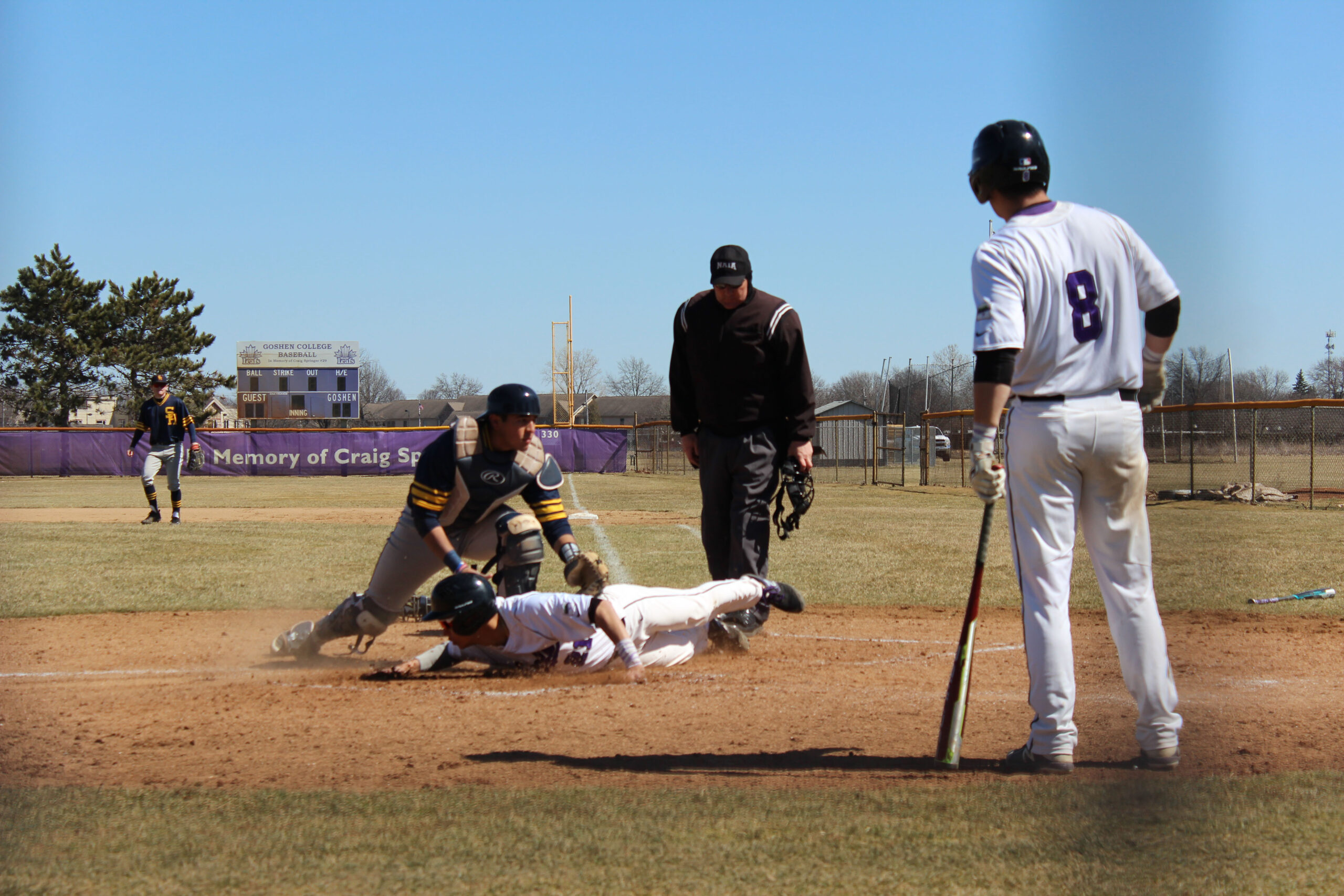 A player on the Goshen baseball team slides into home base during a game