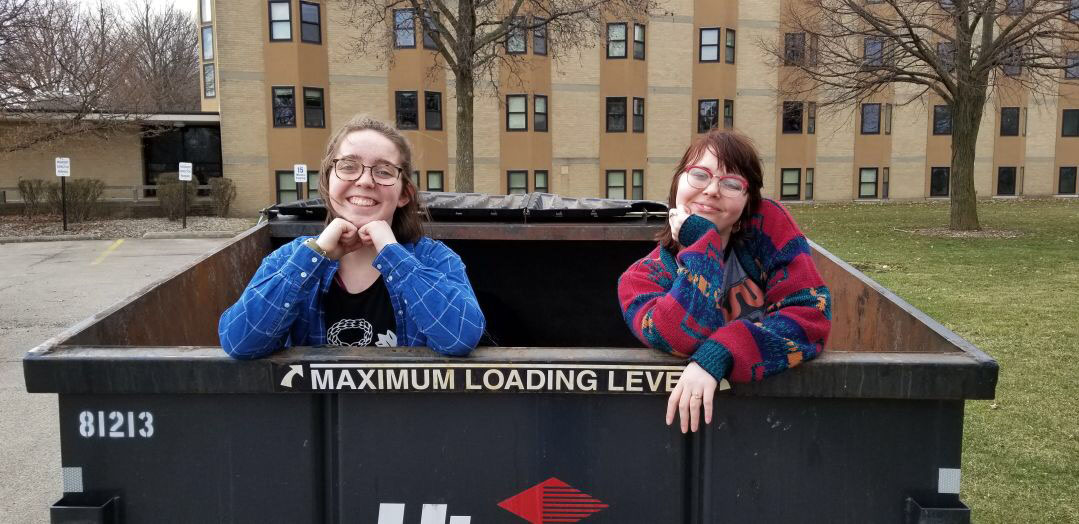 Stephanie Dilbone and Lauren Myers pose for a picture in the dumpster outside Yoder Hall